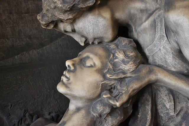 sculpture of man kissing man forehead