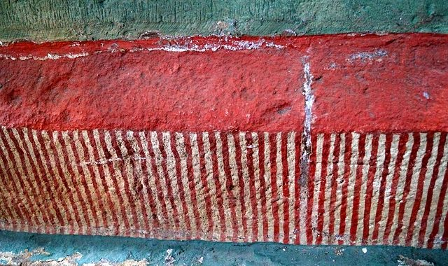 blue red striped art deteriorating on wall